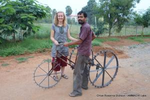 Chloe Rosanna Dickson and manufacturer from Amrita University, Coimbatore, holding first TricTrac tricycle tractor prototype