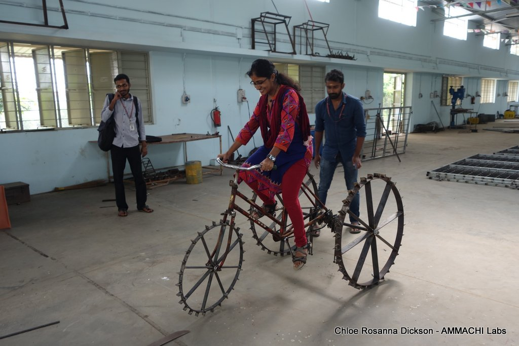 Indian woman testing the TricTrac tricycle tractor inside a manufacturing hall in Amrita University, Coimbatore